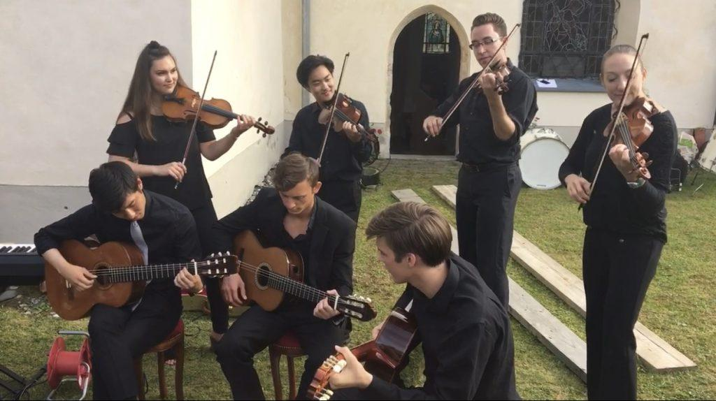 Senior violinist Alexa Birt (second row, far left) and fellow musicians play at St. Stephen's Cathedral in Austria in July 2017, during her summer in the Heidelberg Summer Music Program. The students gave an impromptu outdoor performance of Celtic music after their chamber concert inside the church. Photo courtesy of Alexa Birt