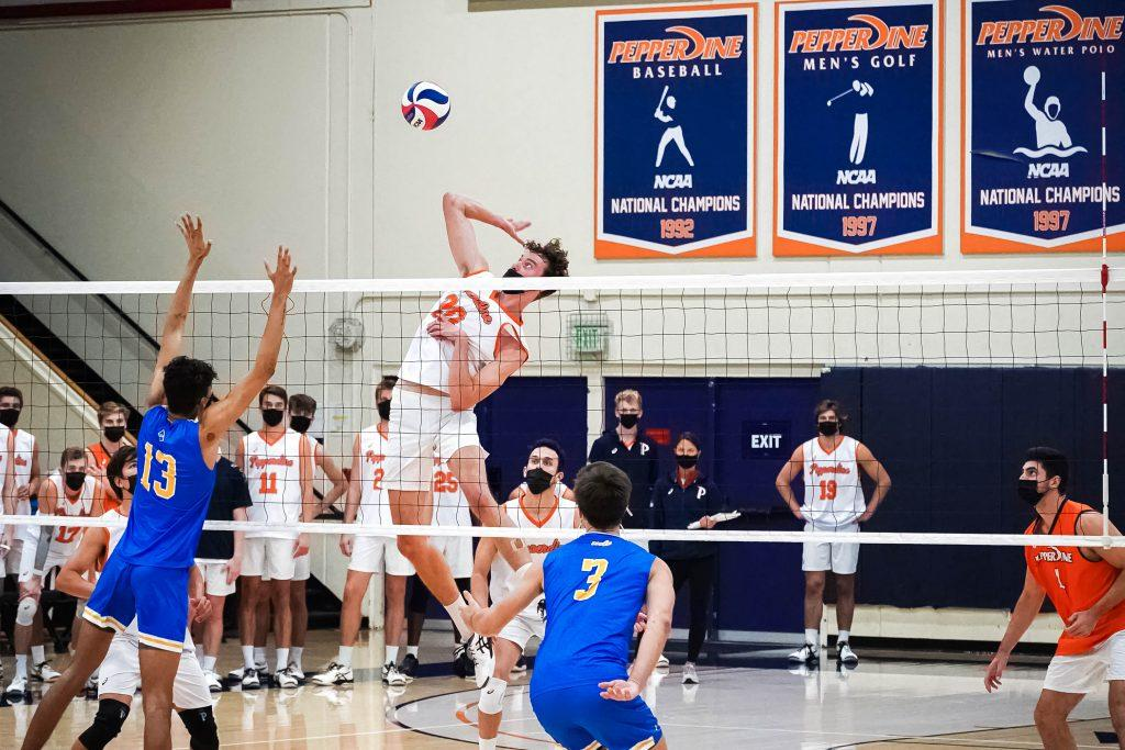 Redshirt senior middle blocker Austin Wilmot slams down a hit against a late UCLA block. Wilmot had an astounding 12 kills and 9 blocks during Saturday's match, earning himself the team's golden wrestling belt, the Mountain Pacific Sports Federation for Defensive Player of the Week and the American Volleyball Coach's Association's National Player of the Week.
