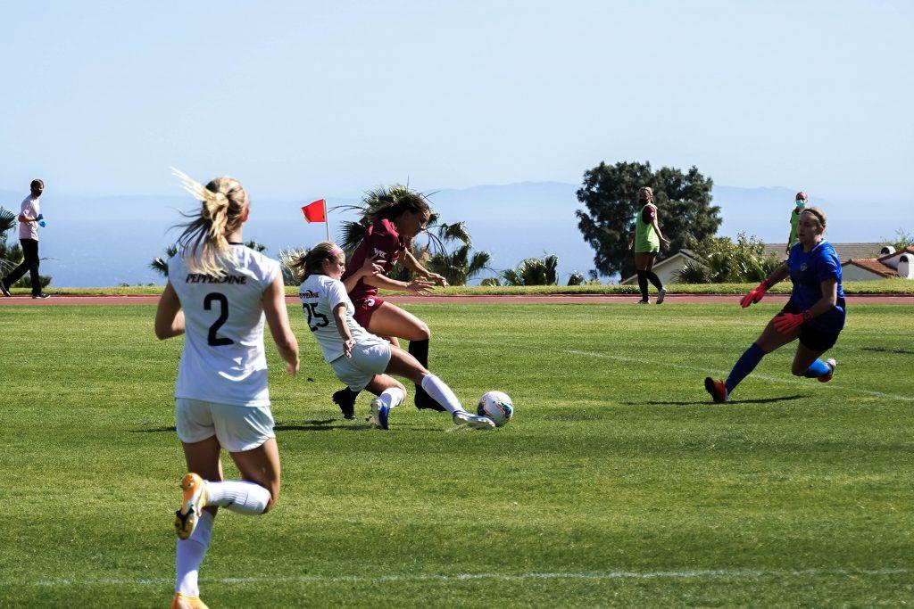 Sophomore forward Shelby Little (No. 25) attempts a sliding shot while guarded by a Santa Clara defender. The Broncos high line forced the Waves to play through balls and try to win footraces to the ball.