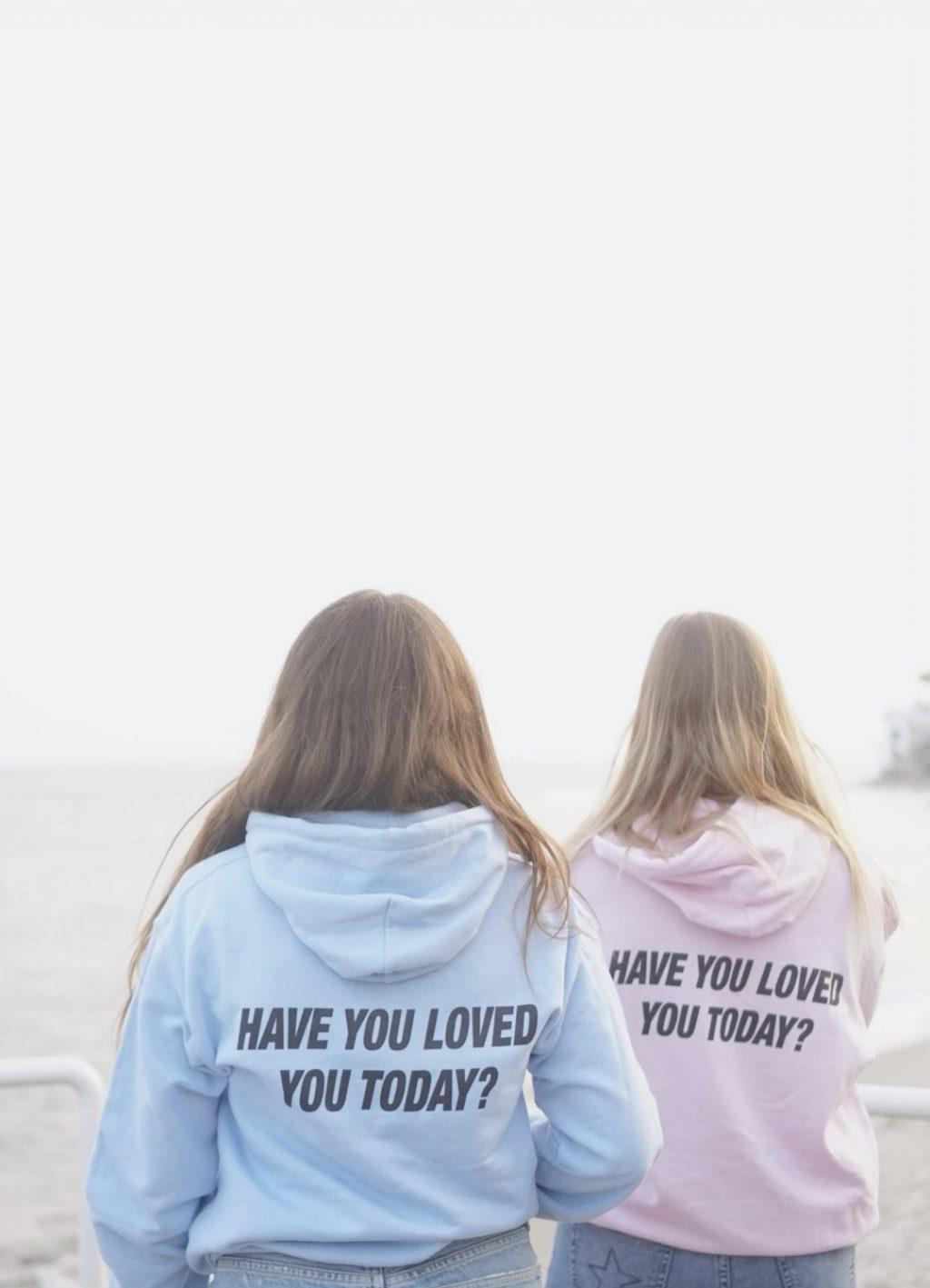 """Sophomores Blakely Huff (left) and Clare Cornelius (right) promote Gearhart&squot;s new company in her """"Have you loved today?"""" sweatshirts in September at Ralphs Beach in Malibu. Gearhart said her main mission is to spread self-love and positivity with her company."""