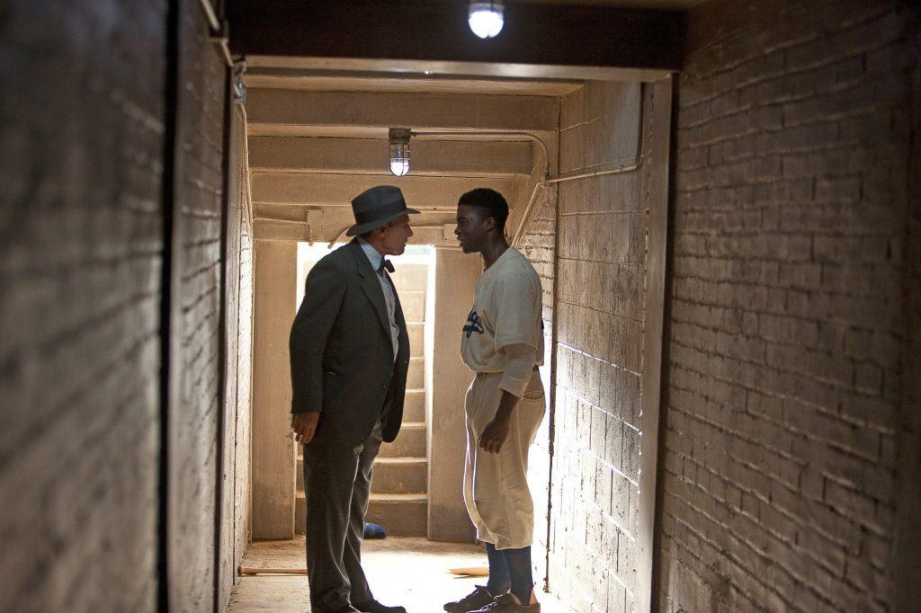 Dodgers owner Branch Rickey (Harrison Ford, left) encourages Robinson after Philadelphia coach Ben Chapman (Alan Tudyk) racially and publicly insulted Robinson off the field. Rickey wanted Robinson to believe in himself because the team counted on Robinson's performance to win.