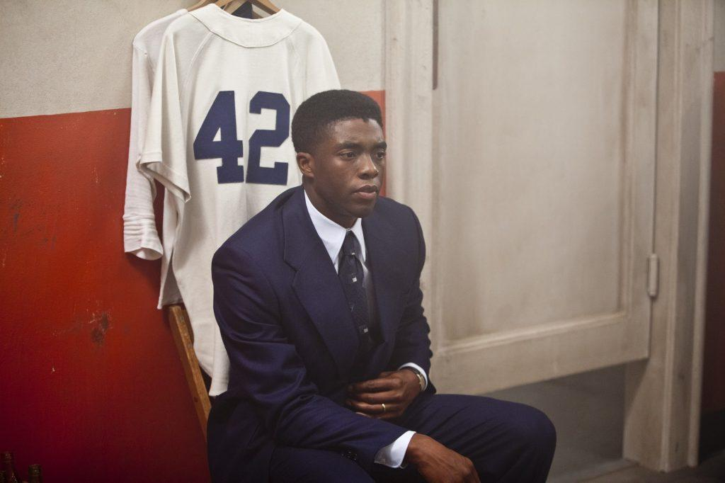 Robinson sits alone on a locker room bench in front of his official Dodgers jersey. Unlike his teammates who had lockers, he only had a hook in the corner.