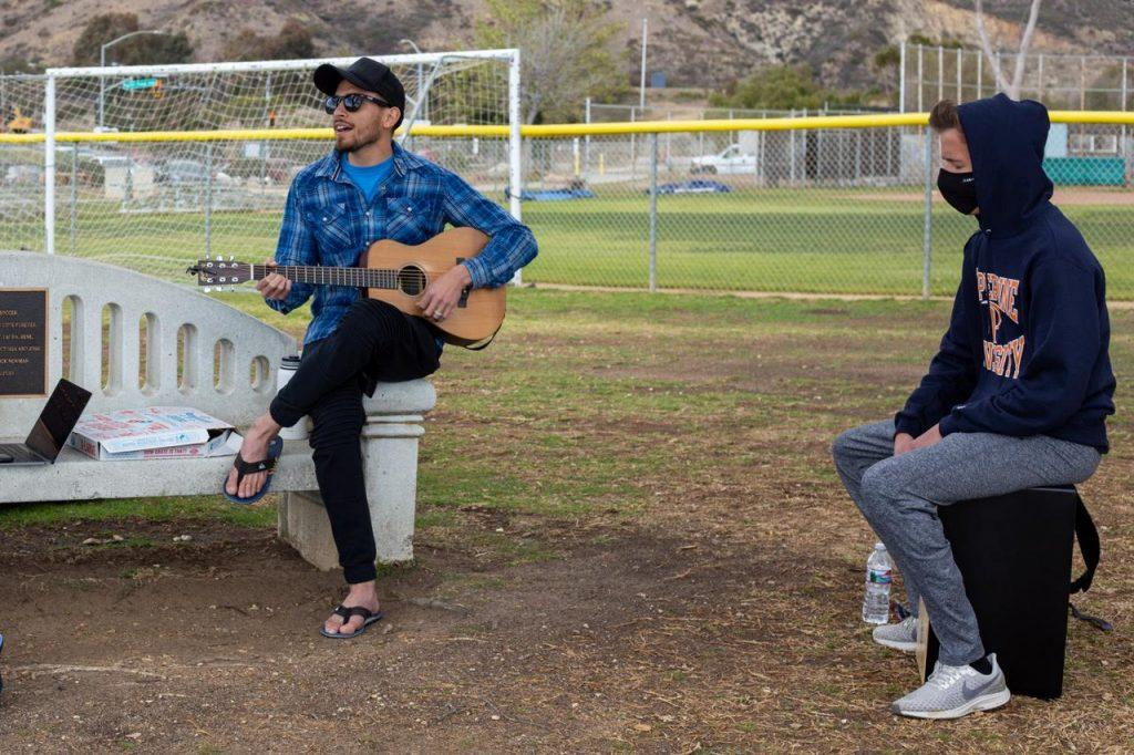 Wiese plays the cajón with Ko Ku, the Vintage worship leader, at Malibu Bluffs Park across the street from campus in March. Wiese said he also plays the violin and was in drumline in high school, but focuses on playing the cajón now because it is more worship-oriented.