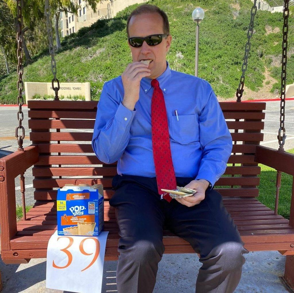 """President Jim Gash eats Pop-Tarts on the Banowsky swing bench in spring 2020. While Gash called this """"the DTR bench,"""" he is in fact mistaken, as this is just A DTR bench, not THE DTR bench. Photo Courtesy of Jim Gash"""
