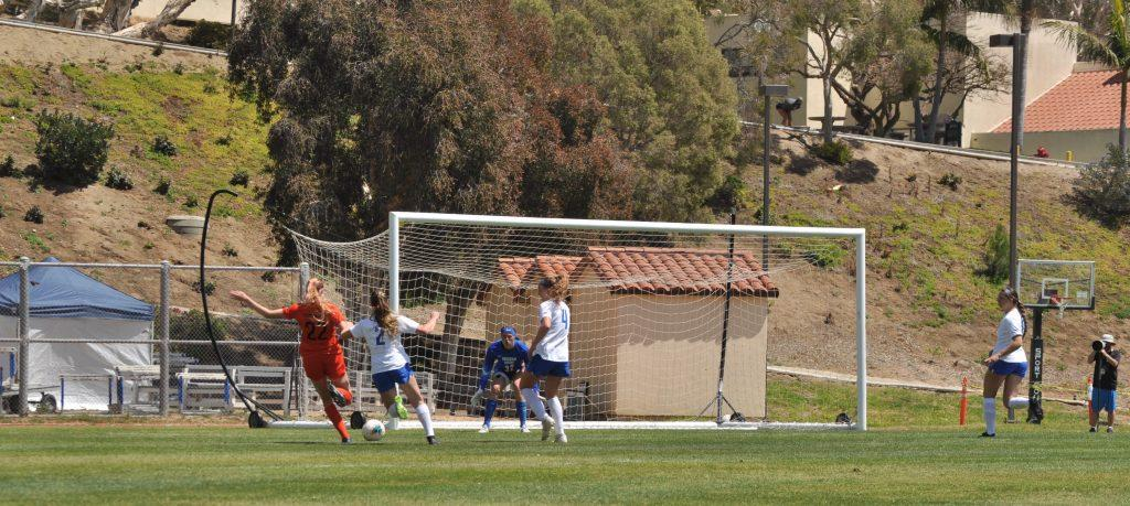 Junior midfielder Leyla McFarland (in orange) shoots and scores during Saturday's match against BYU. McFarland converted her chance, but the Waves missed several other opportunities to score in a 2-1 loss.