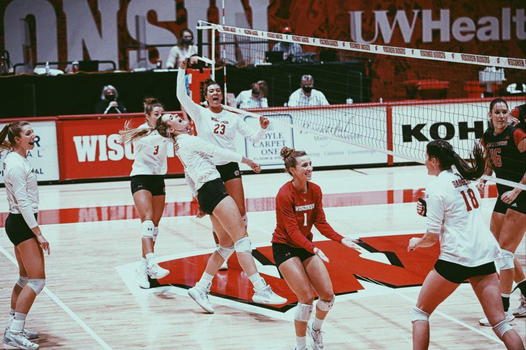 Kraft celebrates by picking up redshirt senior outside hitter Molly Haggerty in a Feb. 6 victory against Rutgers. Wisconsin has seven All-Conference players this season.