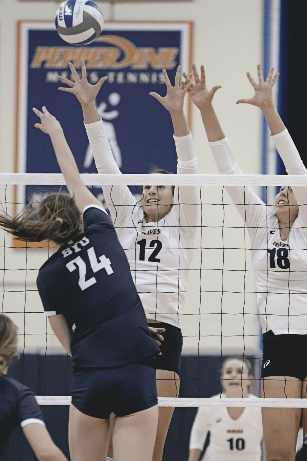 Freshman middle blocker Meg Brown (No. 12) and junior outside hitter Rachel Ahrens (No. 18) elevate for a block attempt Feb. 23. Both Waves were named to the 2021 All-WCC First Team.