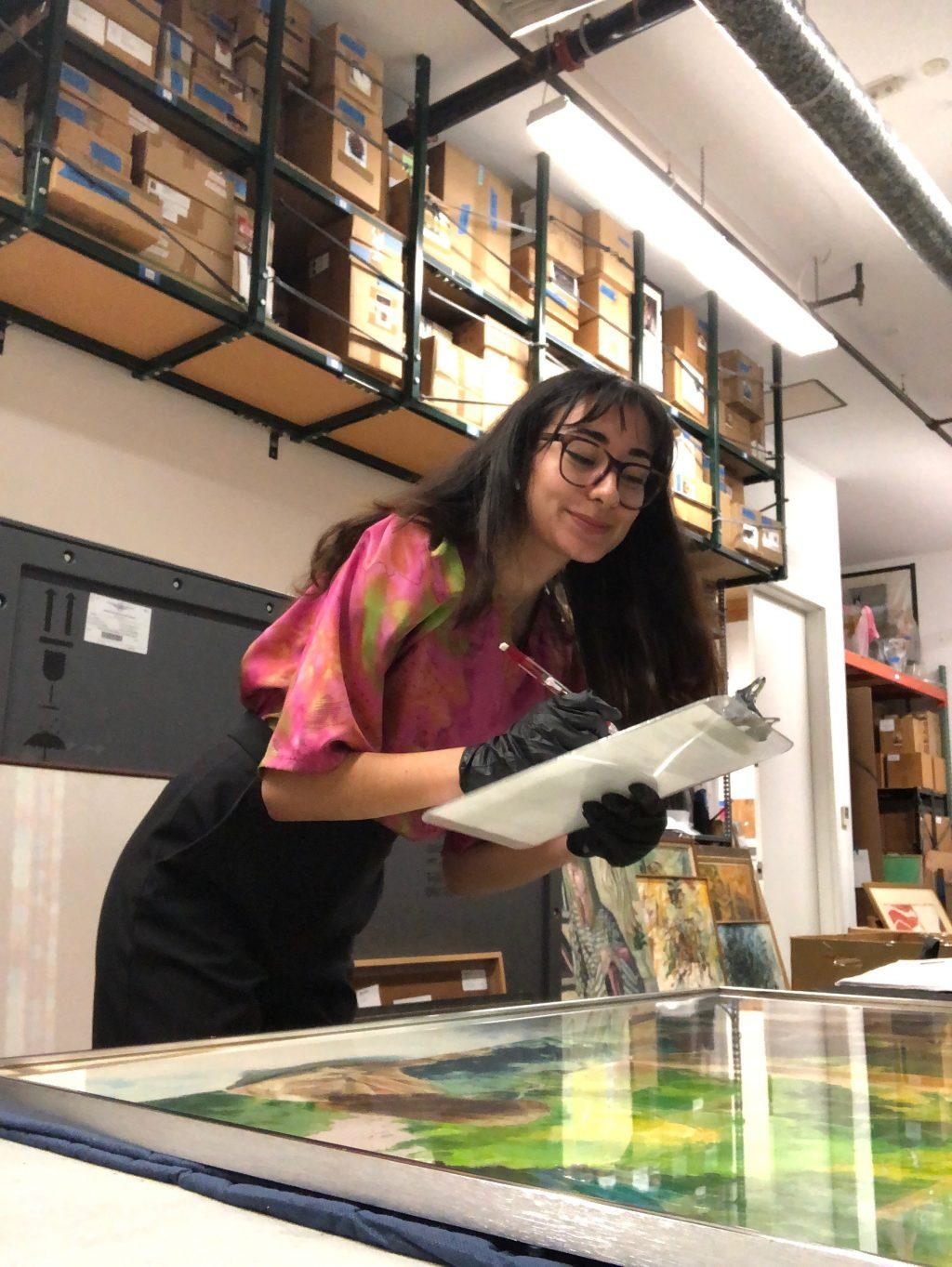 Campbell writes down notes on a painting during her internship in July 2019 at the Long Beach Museum of Art. Campbell said she learned a lot about museum work and local artists through her jobs at both the Long Beach Museum of Art and the Weisman Museum of Art on the Malibu campus.