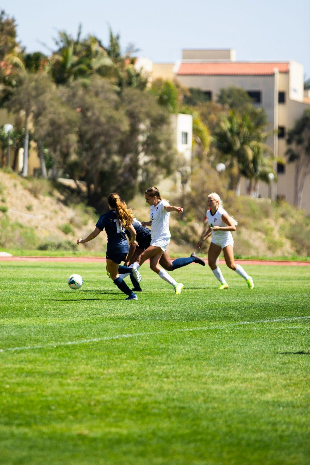 Senior forward Aliyah Satterfield shoots with her left foot between two San Diego defenders in the 88th minute Saturday in Malibu. Satterfield scored on the play, extending the Waves' lead to 7-0.