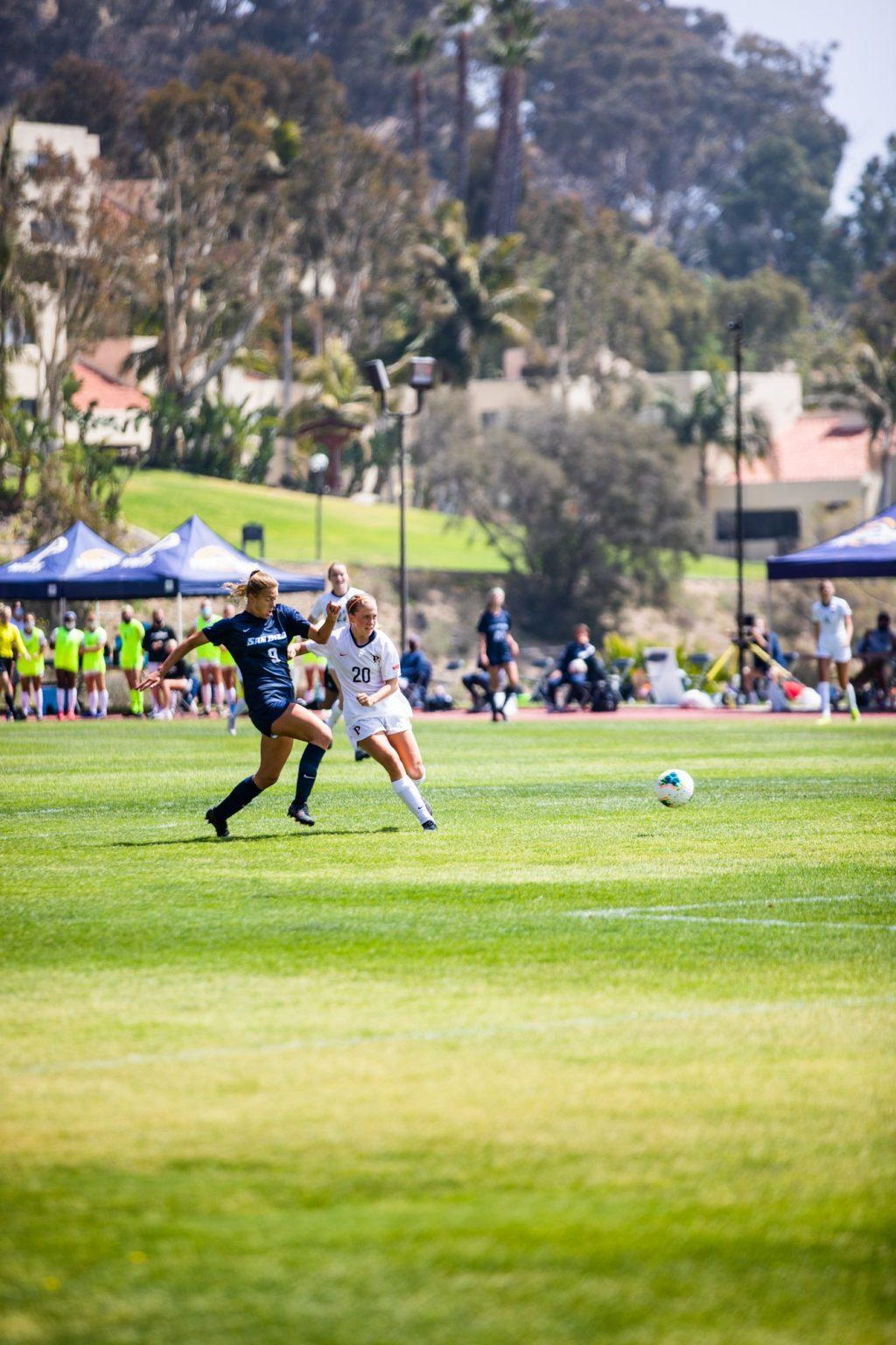Freshman forward Tori Waldeck delivers a composed finish from the top of the penalty area as San Diego freshman Katie Baxter pursues. Waldeck's goal was Pepperdine's fifth in the first 19 minutes of the match and her fourth of the season.