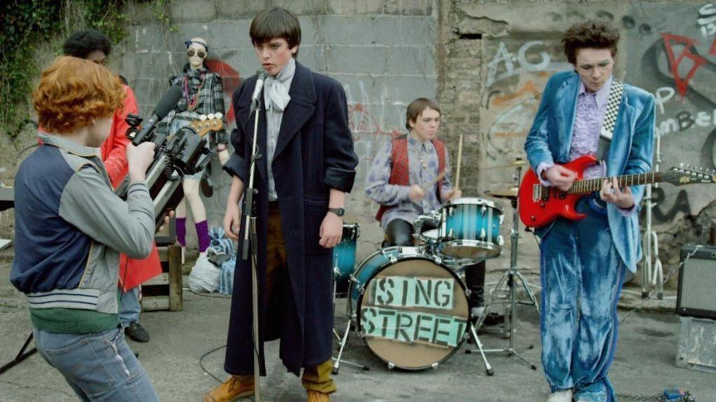 """The band, led by Conor, record a music video for their song """"Riddle of the Model,"""" the first video they filmed with Raphina. Lucy Boynton played Raphina, and she is also known for her role as Mary Austin in """"Bohemian Rhapsody."""""""