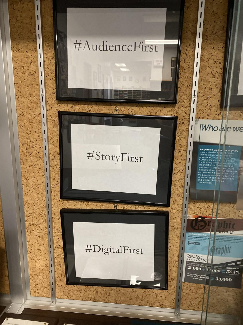 """In the Graphic newsroom, a sign that reads """"Audience First, Story First, Digital First"""" hangs in the trophy case. The Graphic shifted to a digital-first model in the 2010s in an effort to make content accessible online for its audience. Photo by Elizabeth Smith"""