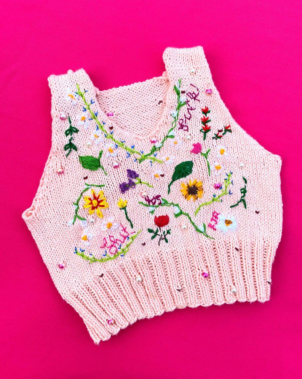 A vest Ross knit in June is photographed on her hot pink kitchen table for an Instagram post that shows off her work. Ross said she has recently started incorporating beadwork into her knitwear, like the floral designs in this piece.