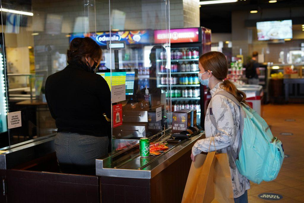 A student purchases a snack from a cashier at the Waves Cafe on June 7. The Caf is open for to-go food service including limited hot daily entree options, grab-and-go sandwiches, salads, fruit cups and desserts.