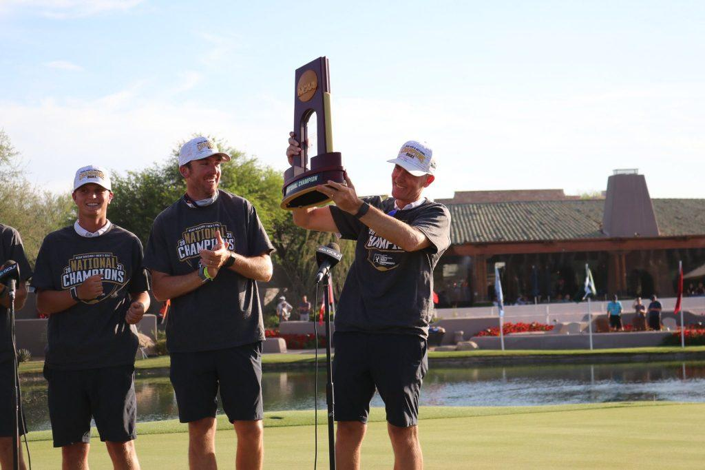 Pepperdine Head Coach Michael Beard raises the trophy high on the 18th green. Beard is in his ninth season as the Waves' head coach, and this is his first national championship and the second in program history.