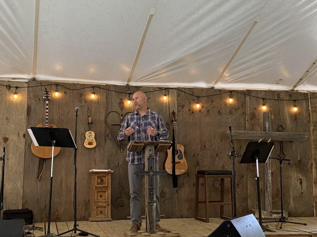 Pastor Brian Kelly speaks to the tent filled with people eager to hear a message, focusing on Acts 20 and the responsibility of loving one another. During the previous school year, the Kellys hosted student nights at their house for the Pepperdine community.
