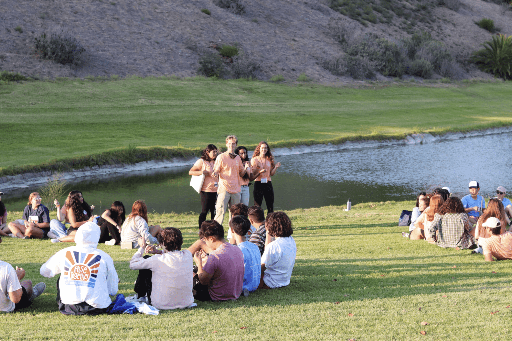 Four Seaside resident advisers lead a group rhythm game on Alumni Park before starting their first Soph Follies practice Aug. 21. There were several bonding games to help the students meet more people. Photo by Ali Levens
