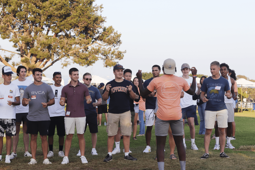 Rockwell Towers resident adviser Timothy Jackson snaps along as he leads the opening section for the group's Soph Follies skit Aug. 21 at Alumni Park. The Year 2 Welcome offered traditions like Soph Follies that sophomores missed out on last year. Photo by Ali Levens