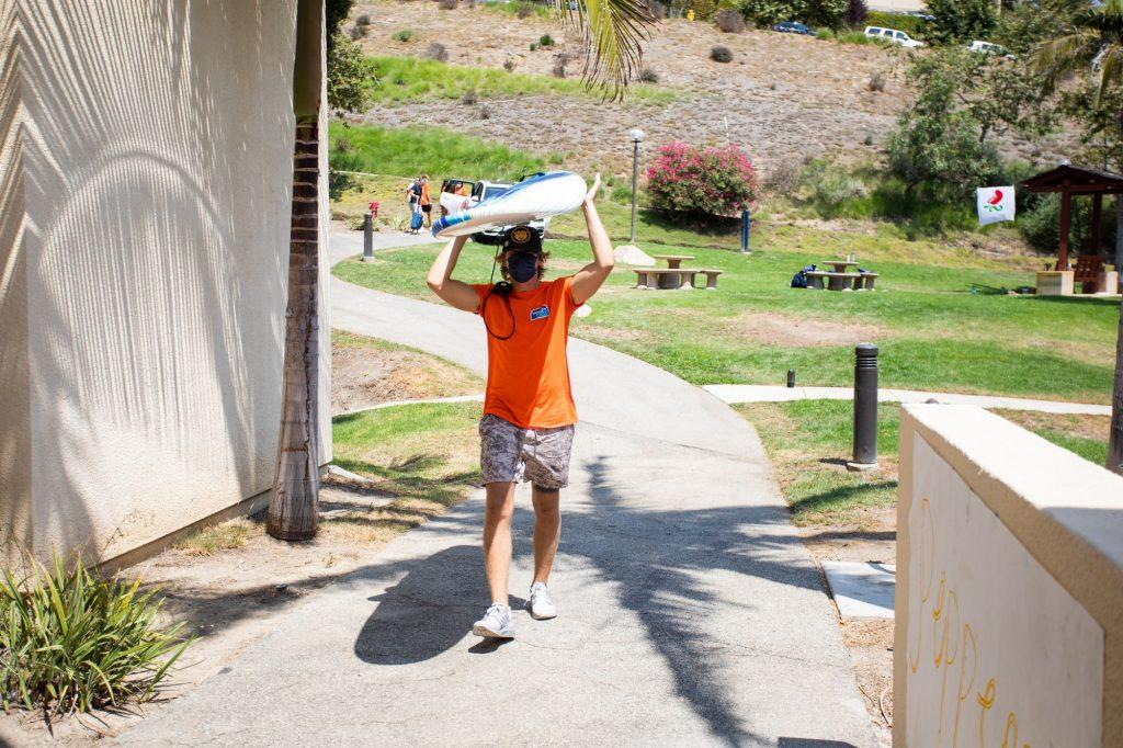 New Student Orientation leader carries in a surfboard for a first-year student moving into Fifield. NSO leaders helped students move in and get settled on campus. Photo by Ryan Brinkman