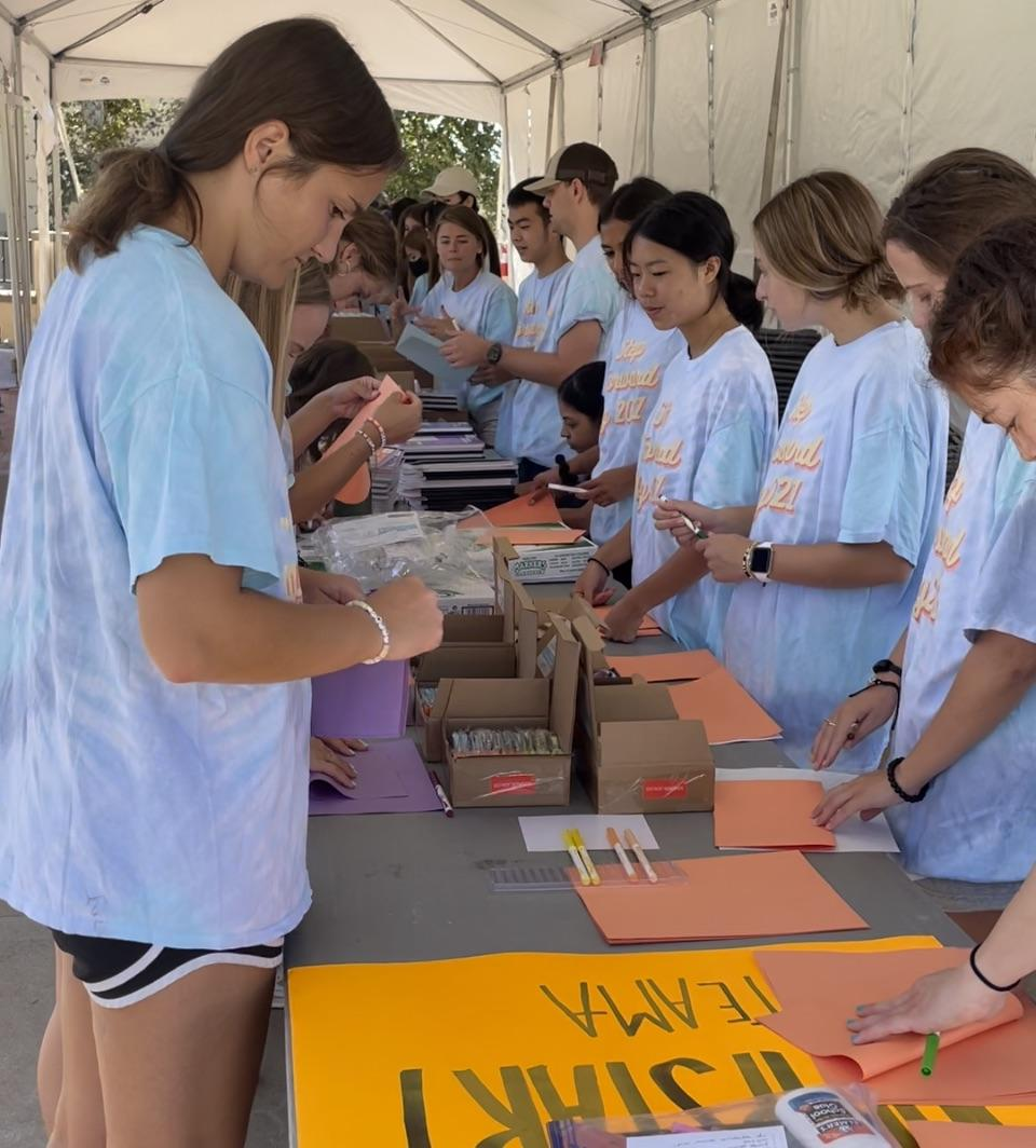 Sophomore Madilyn Henshaw works with other Jumpstart volunteers to put together school supply kits for preschool and kindergarten students. Students came together on the first in-person Step Forward Day since 2019 to do hands-on service activities.