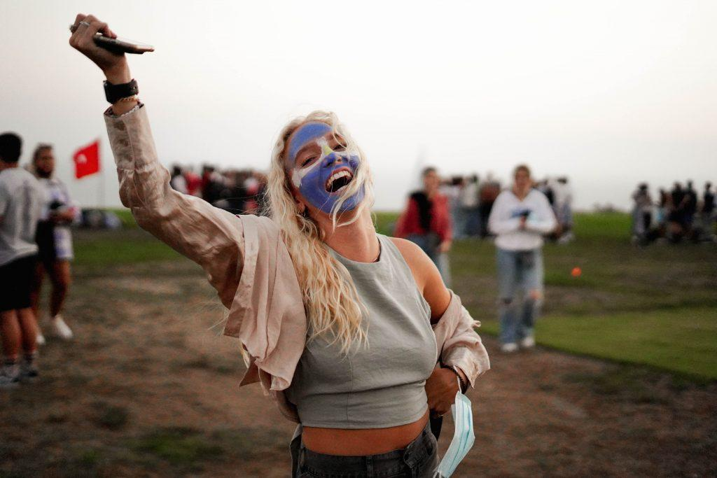 Sophomore Courtney Wisniewski smiles at the camera with her face painted with the Argentine flag. Although the Return was mainly for first-year students and IP alumni, some sophomores and juniors also attended the event in support.