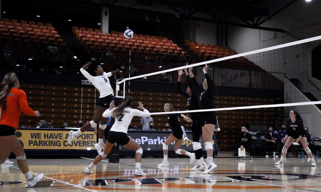 Senior middle blocker Rosie Ballo spikes the ball against the Huskies. Ballo finished the match with six kills and two blocks.