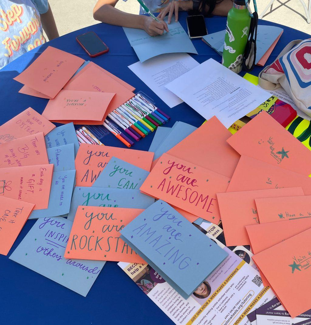 Students write positive messages to be put in supply kits for children and families in need. The directors of Step Forward Day put extra budget money into supplies this year rather than using it to take all students off campus.