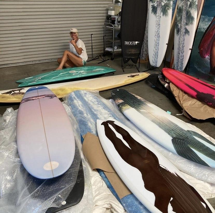Bobbi Bennett sits on the ground and works on creating her art on her boards. Bennett said COVID-19 gave her more time to focus on learning how to shape boards.