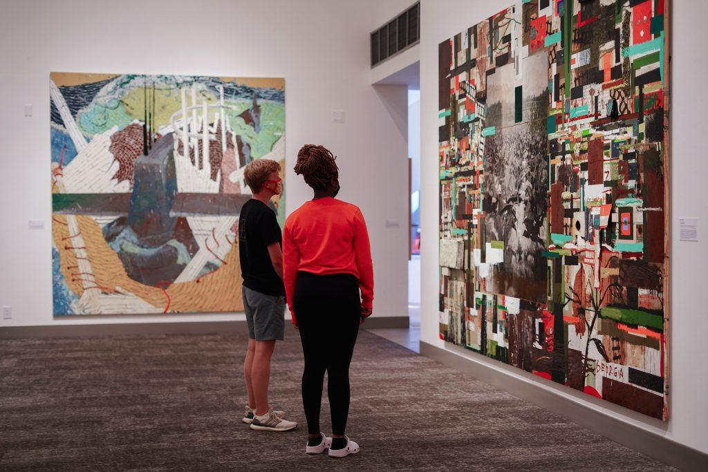 """Two students view an """"Environmental Reflections"""" piece at the Weisman Museum. Students can access the exhibit for free, but they must reserve timed-entry tickets from the museum&squot;s website. Photo by Dane Bruhahn"""