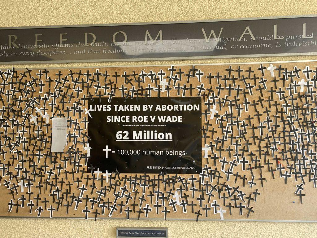 """A display on the Freedom Wall shows 62 cut-out crosses and a sign that claims that abortion has taken 62 million lives since the 1973 Roe v. Wade SCOTUS case. The PCR posted this display Sept. 28 to acknowledge the """"atrocity"""" of abortion, wrote the PCR in an email to the Graphic. Photo by Anitiz Muonagolu"""