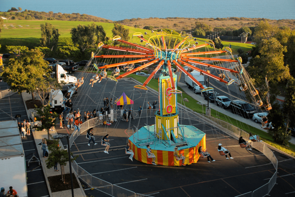 The carnival swing flies over the Firestone Fieldhouse parking lot at Madness VIllage. Madness Village had a Sizzler ride, a Ferris wheel, student activity vendors and free food to celebrate Waves Weekend. Photo by Ella Coates
