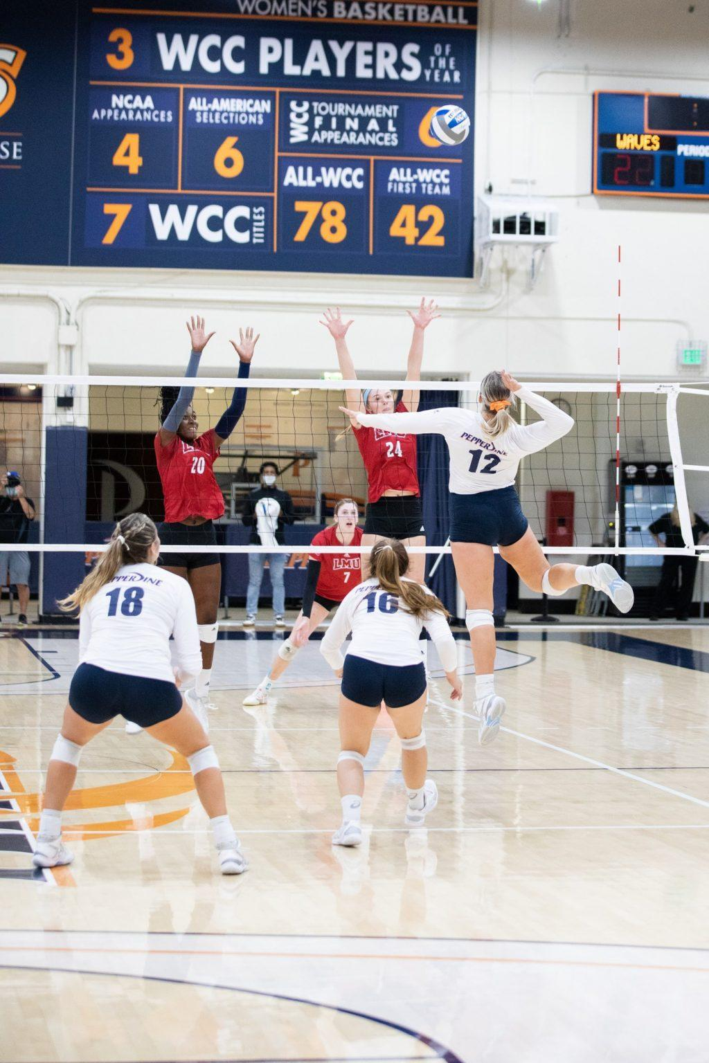 Sophomore middle blocker Meg Brown goes for a spike against LMU blockers Oct. 2. The Waves have a six game win streak, with Brown starting each match.